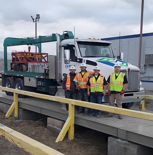 Michelli team poses with a heavy duty test truck on a truck scale