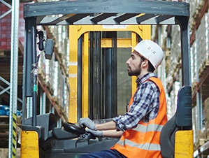 Worker in a forklift using a forklift scale