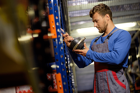 Worker grabs spare part from shelf in warehouse